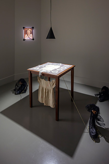 "Füsun Onur, ""War through the Eyes of a Child"", 1994. Table, photographs, boot, doll, baby dress. Installation view: ""Through the Looking Glass"", ARTER, 2014. Photo: Murat Germen."