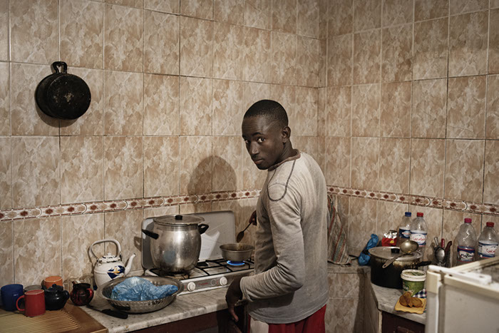 Valentino Bellini and Eileen Quinn, Limbo, 2015. 17-year-old Bassur, immigrant from Senegal, is portrayed in his kitchen making dinner. Bassur arrived in Zarzis in April 2015, rescued at sea by local fishermen. He now lives with Adama and Dousu in Zarzis.